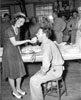 Young lady feeding a piece of cake to the chaplain during an organizational party.